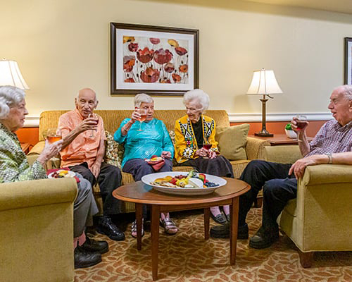 Group of 5 seniors gathered around, sitting on sofa and chairs with drinks and food tray on table in front of them talking