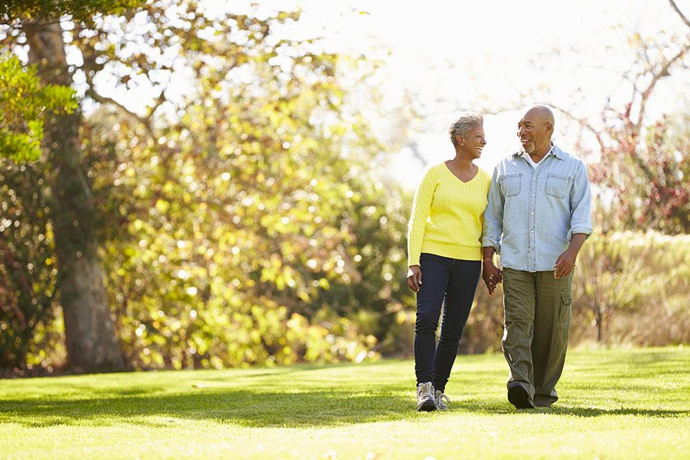 Happy senior couple walking on nice summer day outside