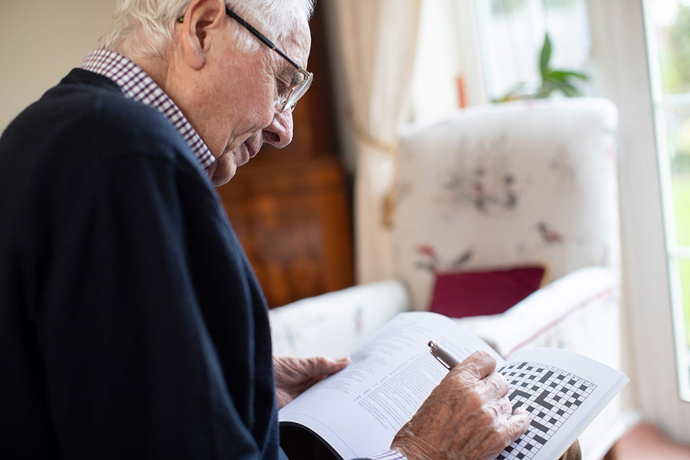 Senior man sitting in assisted living community doing crossword puzzle
