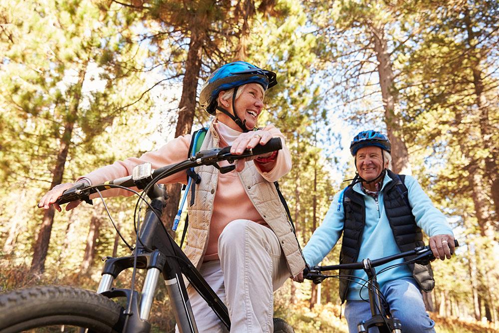 Happy senior couple riding bikes outside