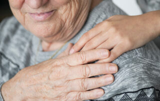 Close up of senior sitting down with hand on shoulder touching caregivers hand on shoulder