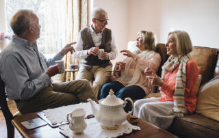 Group of seniors in assisted living talking and drinking coffee