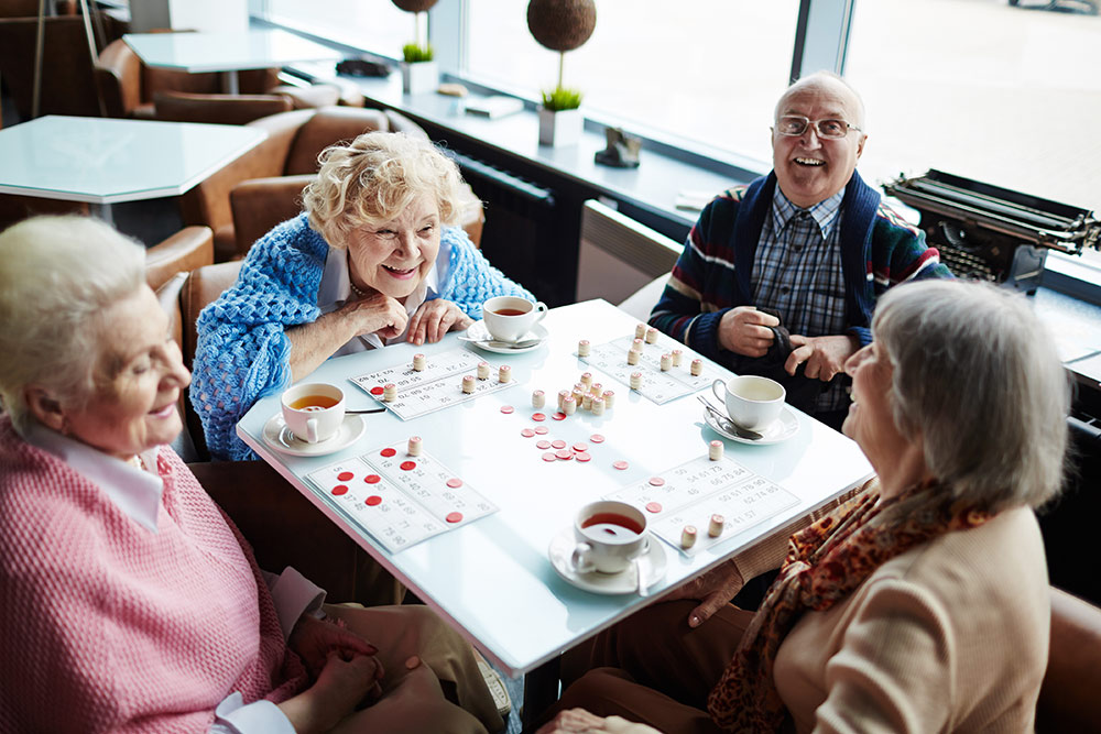 Group of seniors sitting at table playing bingo in memory care services