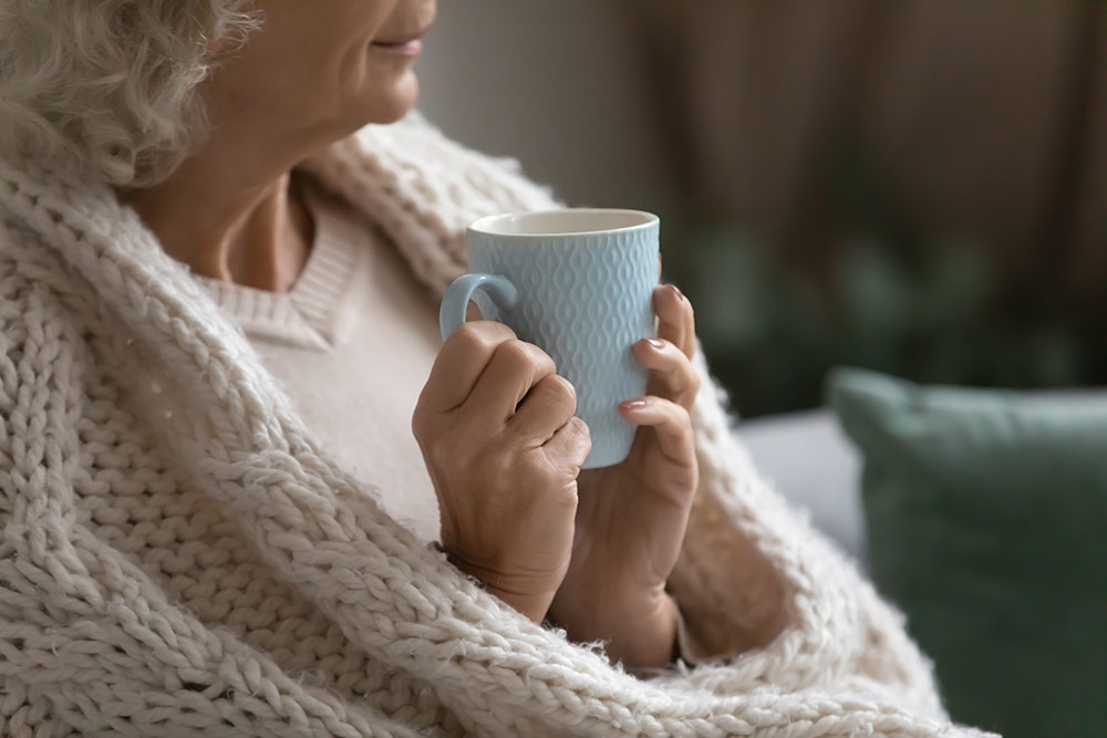 Close up of woman wrapped in blanket sitting on couch with cup of team in hands