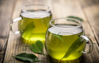 Close up of two cups of green tea on wooden table