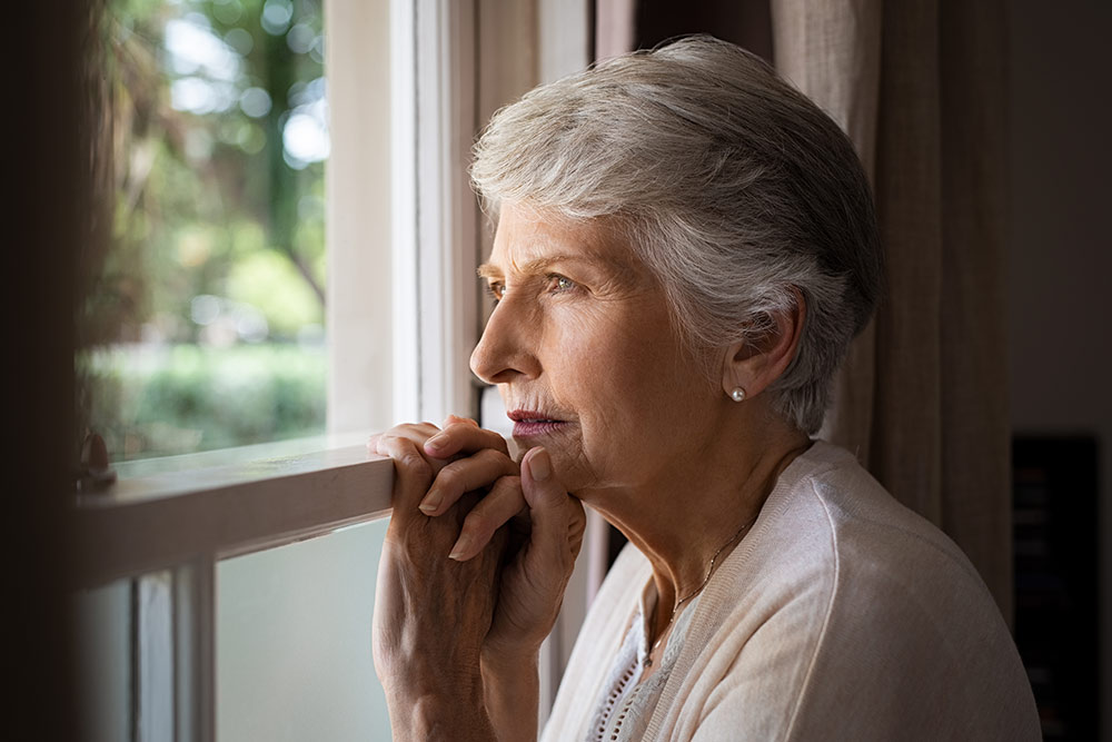 Senior woman with dementia looking lost out window