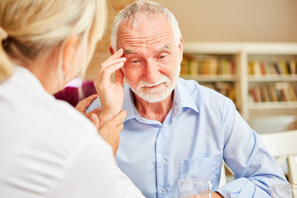 Senior man with dementia holding head with caregiver with him consoling him