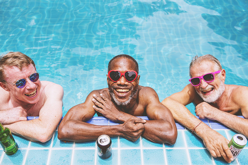 Three senior men smiling and laughing in pool with drinks and sunglasses