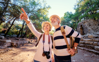 Senior couple hiking outside in wilderness with cameras around necks