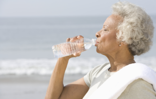 Senior woman outside by beach, drinking water