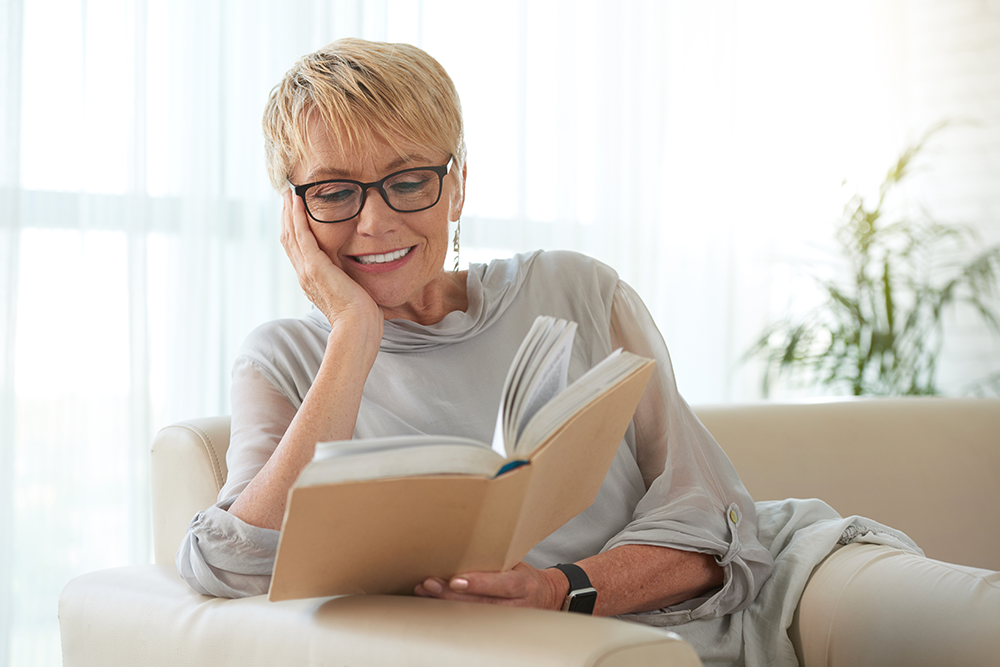 Woman sitting on couch relaxing and reading a book