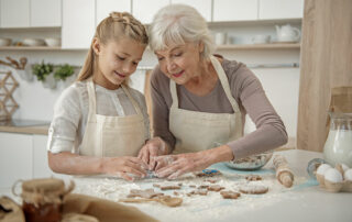 Senior woman baking in kitchen with granddaughter