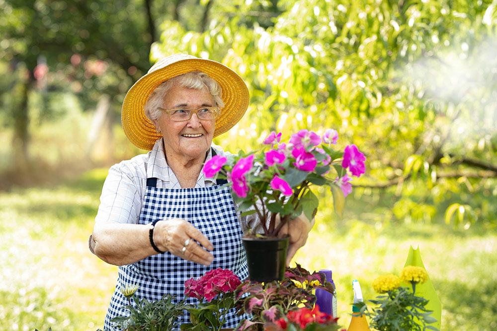 Senior woman tending to container garden in senior living in Carlsbad