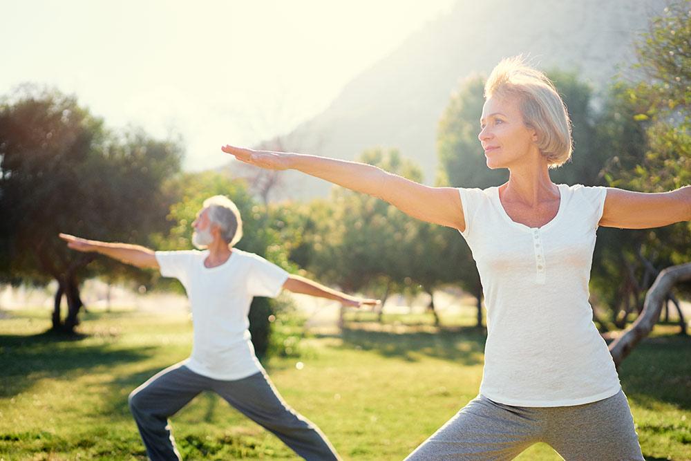 Seniors outside doing yoga